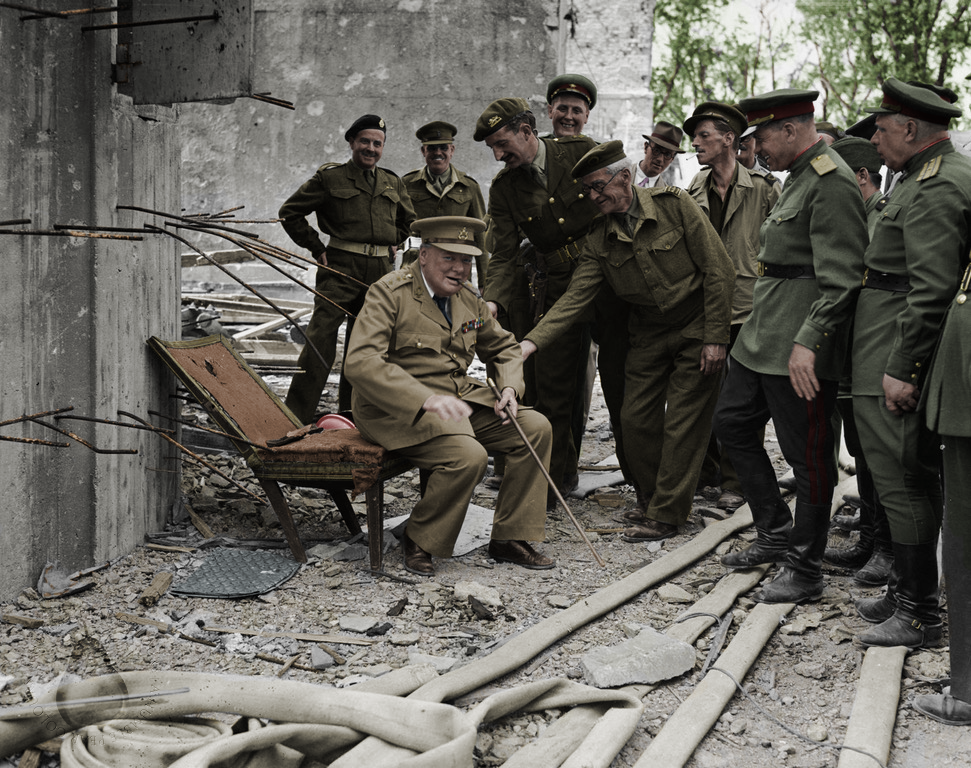 Winston Churchill sitting in the remains of Hitler's armchair, July 1945