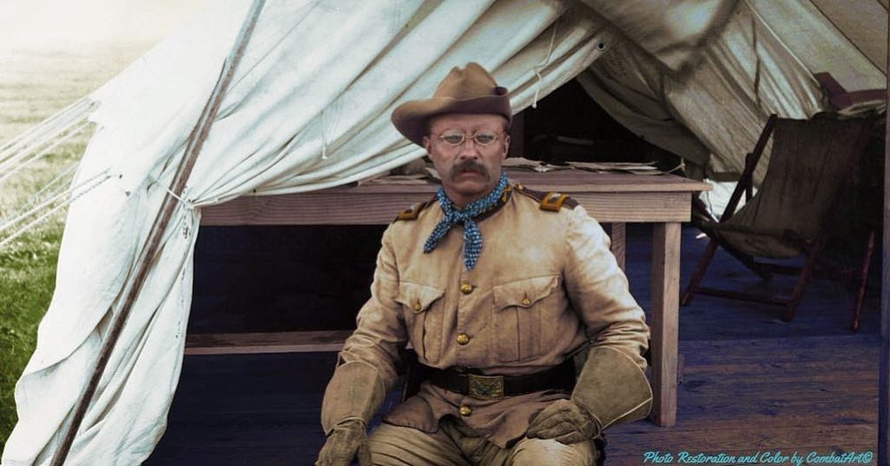 Colonel Theodore Roosevelt sitting outside of a tent in his Rough Riders uniform during the Spanish-American War in c. 1898. Colorization by  Combat Art
