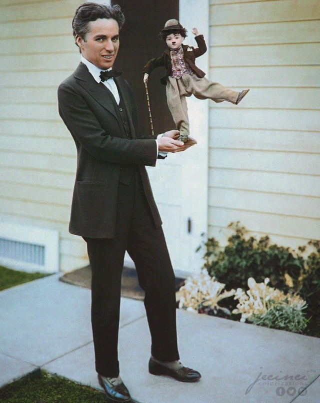 Charlie Chaplin holding a puppet version of his character The Tramp in c. 1914