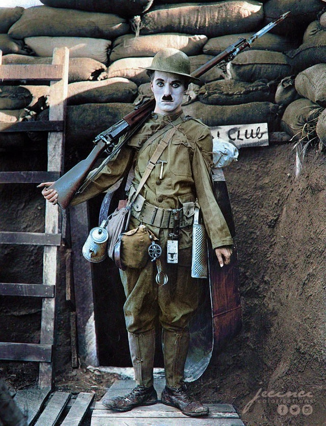 """Charlie Chaplin starring as """"The Tramp"""" in the 1918 film """"Shoulder Arms"""" which was directed, written and produced by himself."""