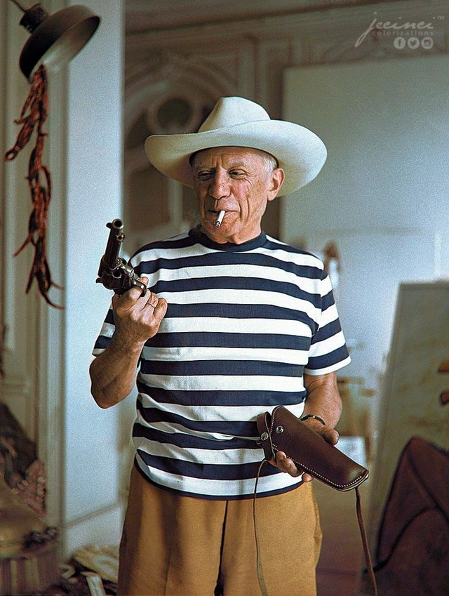 Pablo Picasso wearing a hat and holding a revolver & holster given to him by Gary Cooper in Cannes, France in 1958. Colorization by  Jecinci