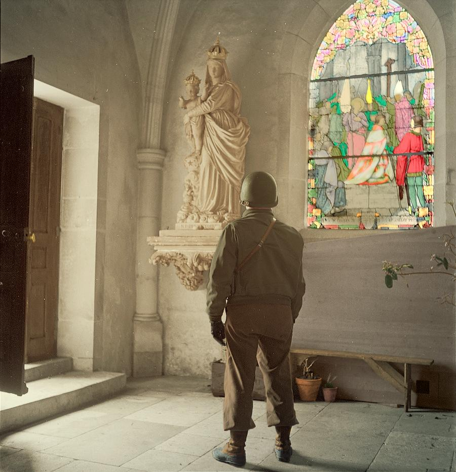 Photograph of an American soldier standing inside a church somewhere in Europe, 1945