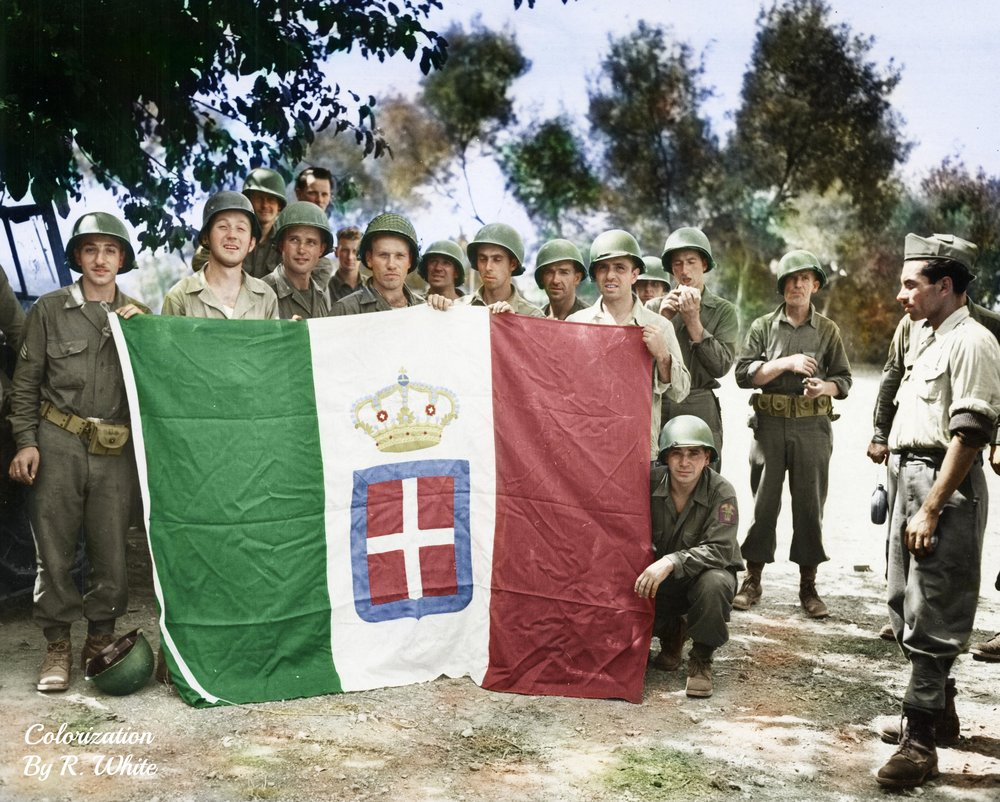 Photograph of American soldiers holding up a captured Italian flag in Paestum, Italy, September 1943.