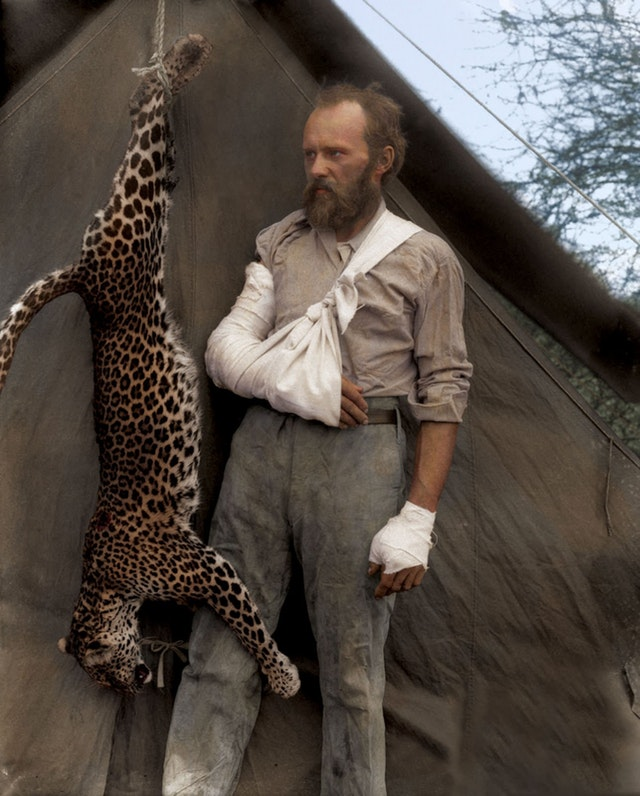 Photograph of Carl Akeley standing next to the leopard he killed with his bare hands after it attacked him, 1896