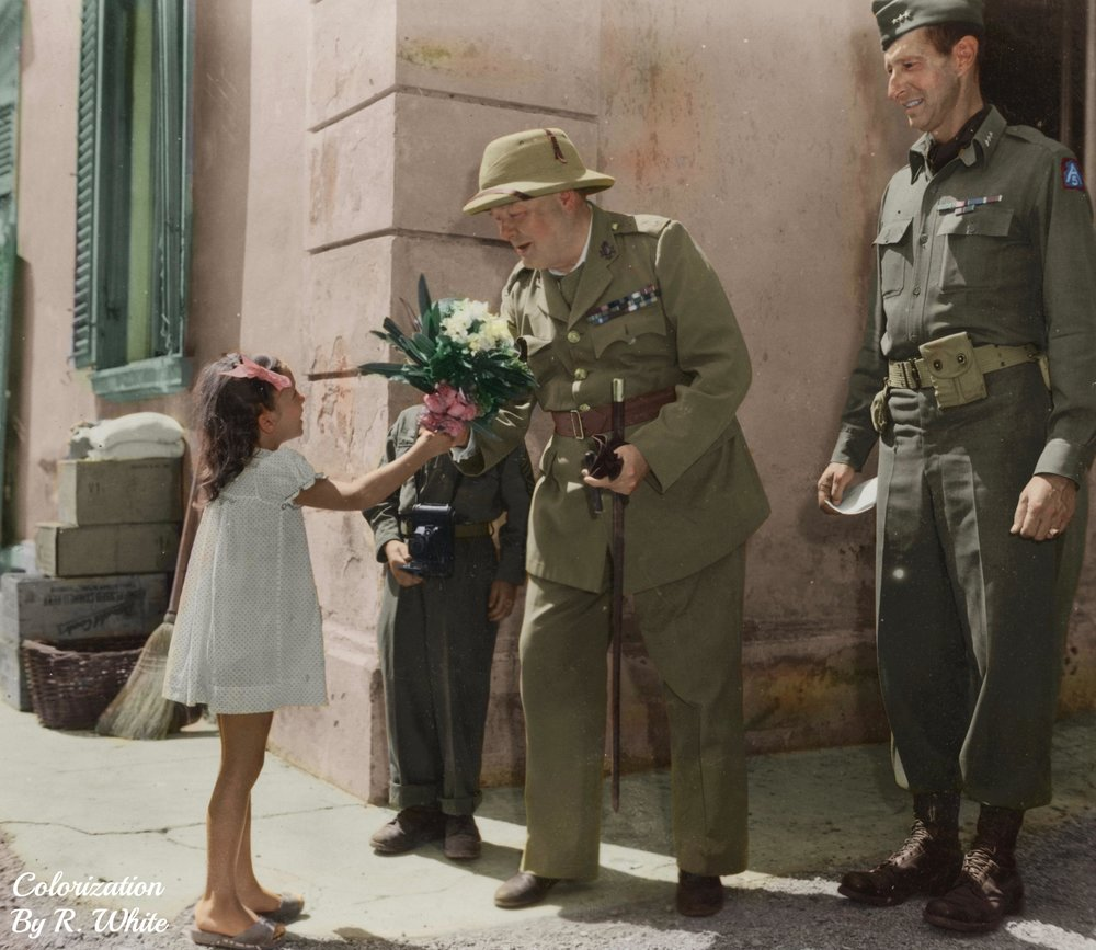 Photograph of Prime Minister Winston Churchill and Lieutenant General Mark Clark receiving flowers from a child in Castiglioncello, Italy, 19 August 1944