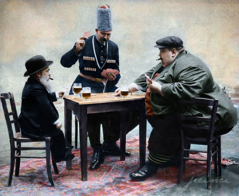 Photograph of the tallest, shortest, and fattest men of Europe drinking and playing a game of cards together, 1913