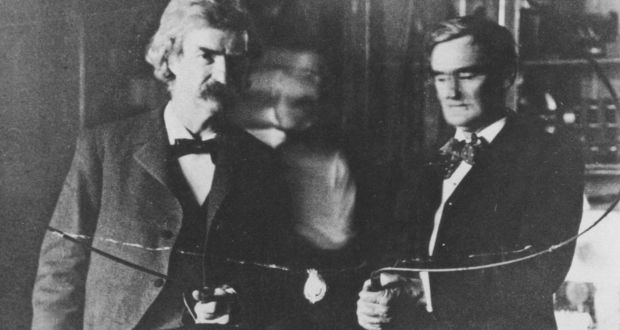 Nikola Tesla (blurred in the centre) performing an experiment with author, Mark Twain, and actor, Joseph Jefferson, in 1894.