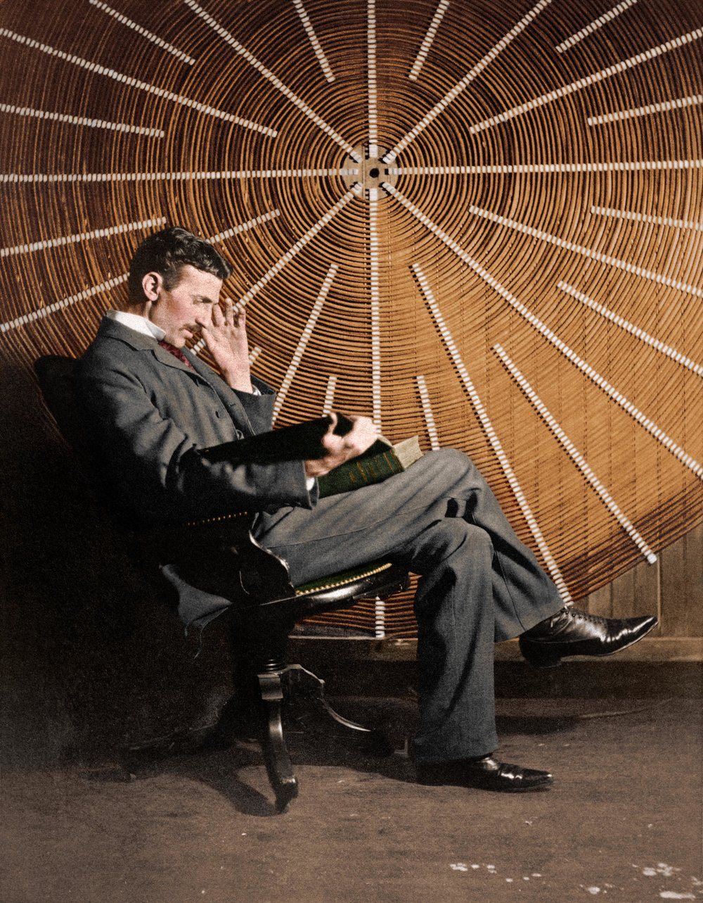 Scientist and Inventor, Nikola Tesla, reading 'Theoria Philosophiae Naturalis' by Roger Boscovich in front of the spiral coil of his high-frequency transformer in New York, USA in 1896. Colorization by  Mads Madsen