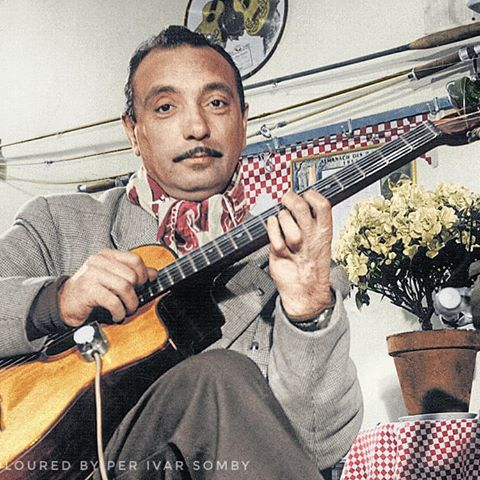 A photo of Django Reinhardt with his guitar in his 40s towards the end of his life in c. 1950. Colorization by  Per Ivar Somby