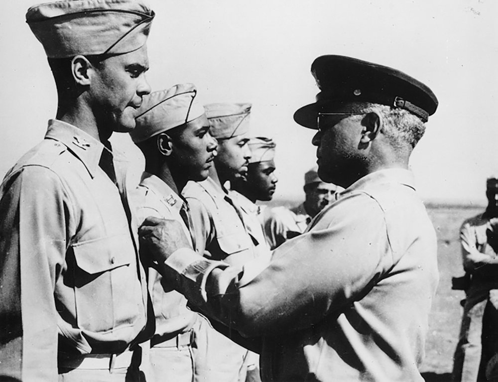 Colonel Benjamin O. Davis Jr. (left) receiving the Distinguished Flying Cross from his father, Brigadier General Benjamin O. Davis Sr. at Ramitelli Airfield. Italy in September 1944.