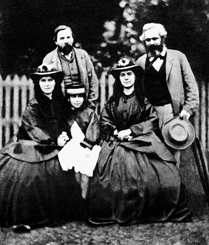 Karl Marx and Friedrich Engels with Marx's daughters Jenny Caroline, Jenny Julia Eleanor, and Jenny Laura in c. 1864.