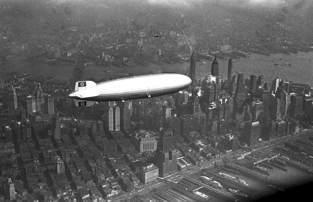 A black and white photograph of the LZ 129 Hindenburg flying over Manhattan, New York City, United States on the 6 May 1937, just hours before it would be destroyed in a fire while trying to dock in New Jersey.