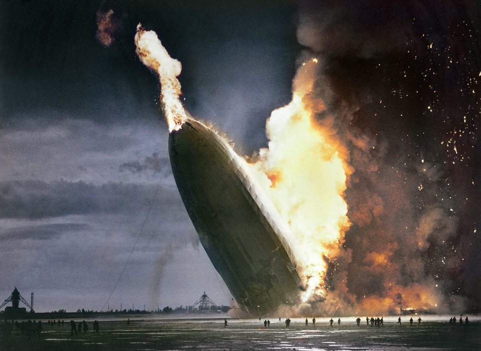A colorized photograph of the Hindenburg disaster on the 6 May 1937 at the point where it hit the ground. With the color you can see just how large of an area of the sky is covered by smoke and fire. Colorization by  Dana R. Keller
