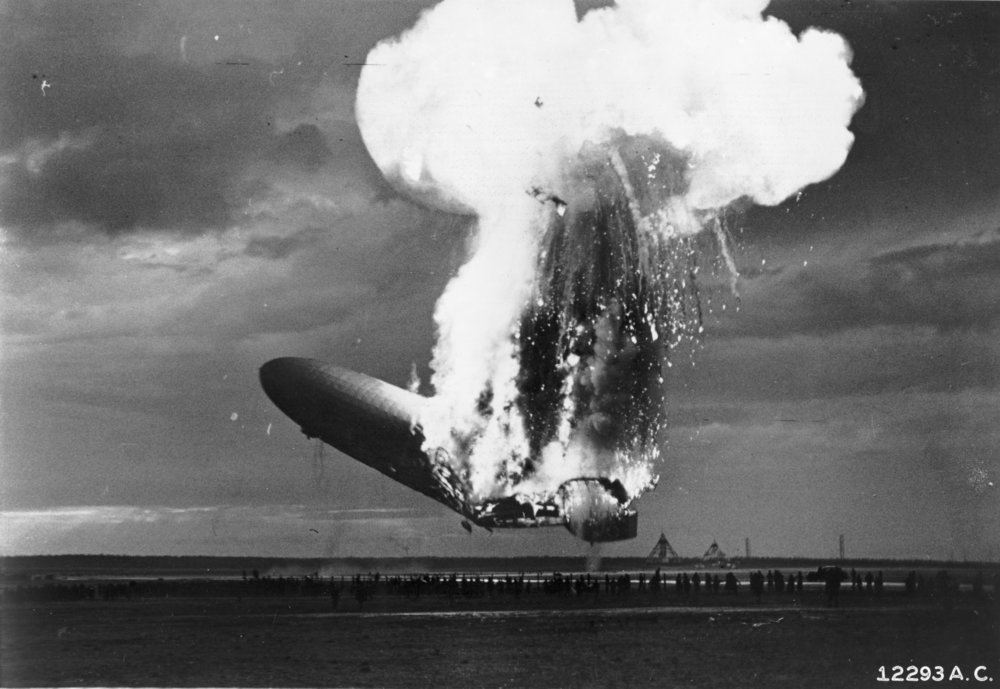 A black and white photograph of the Hindenburg on fire before it has hit the ground.