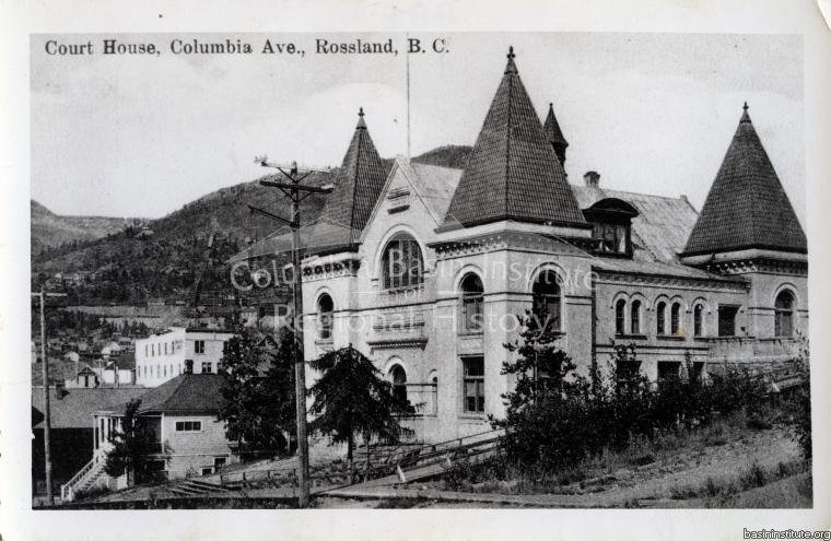 2276.0011 Postcard - Rossland Court House . Notice Landcaster Rooming House  (white) in the background