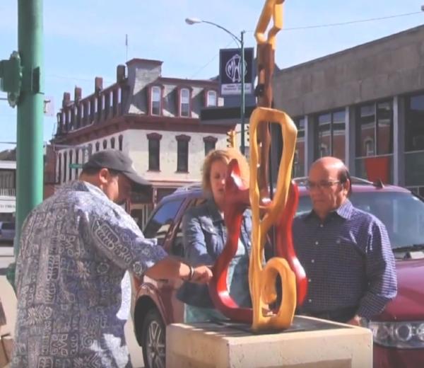 A family checks out a sculpture at Decatur Sculpture Tour. Listen To The Music, Curtis Rose