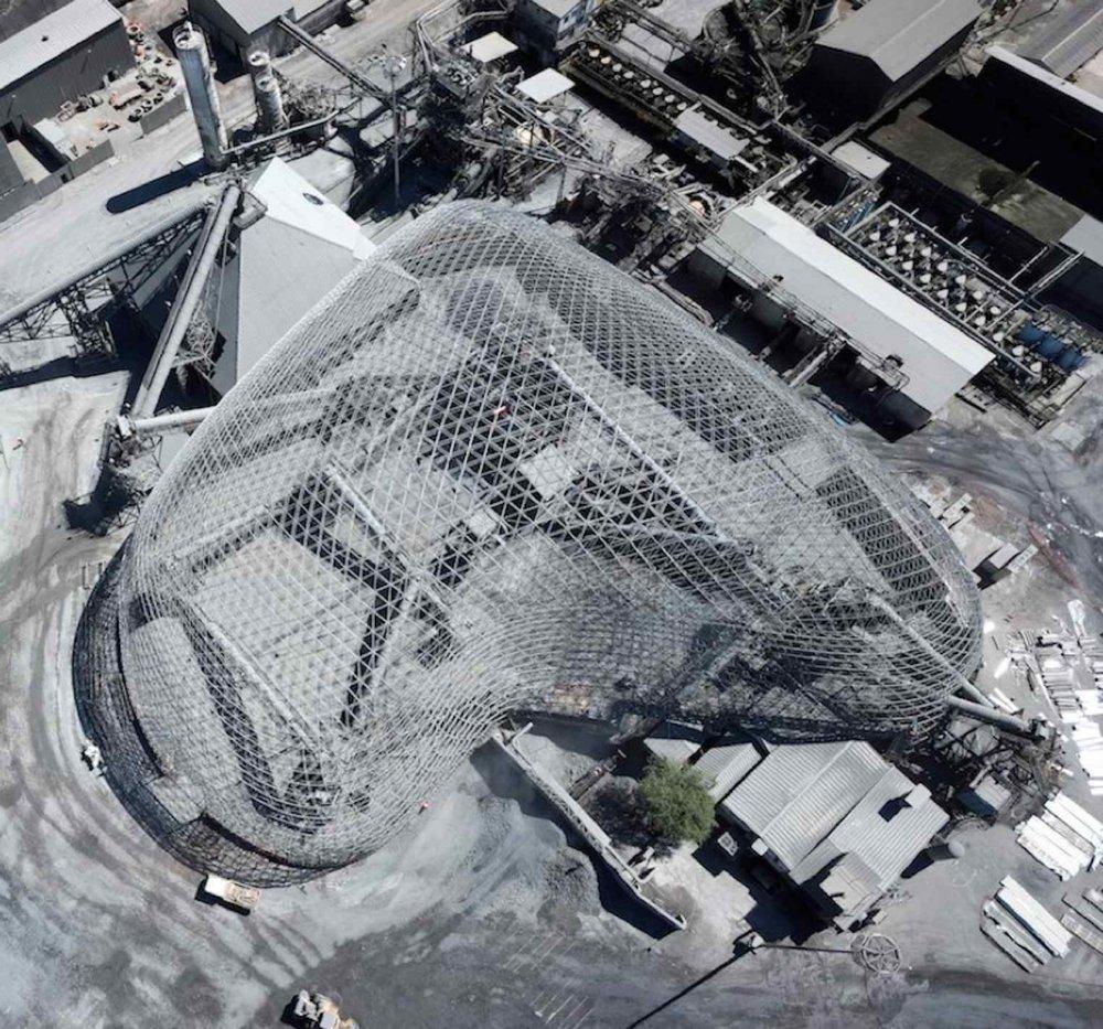 La forma irregular del domo de procesamiento de mineral de cobre se alza 90m sobre una pila de almacenamiento, además de equipo y edificios.