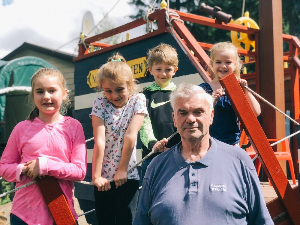 Don with a handful of his grandkids on the custom play pirate ship he built for them in his yard