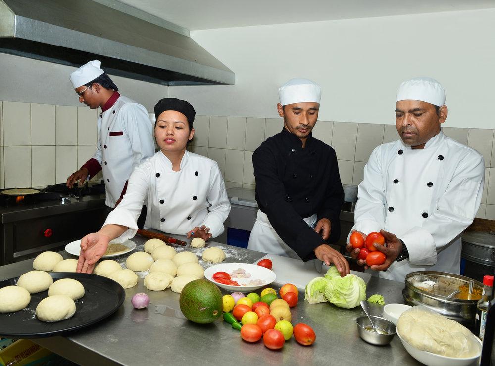 Sarangi kitchen staff proud to be wearing uniforms designed and made by Sarangi Social Enterprise