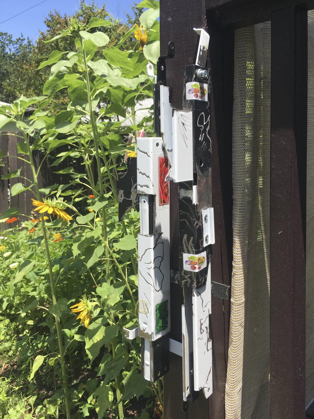 "Nathan Ellefson    skunkcore/originalchapstik/secondhandcopcar   modified projector mounts, food packaging, tape  9"" x 22"" x 4"", 2018"