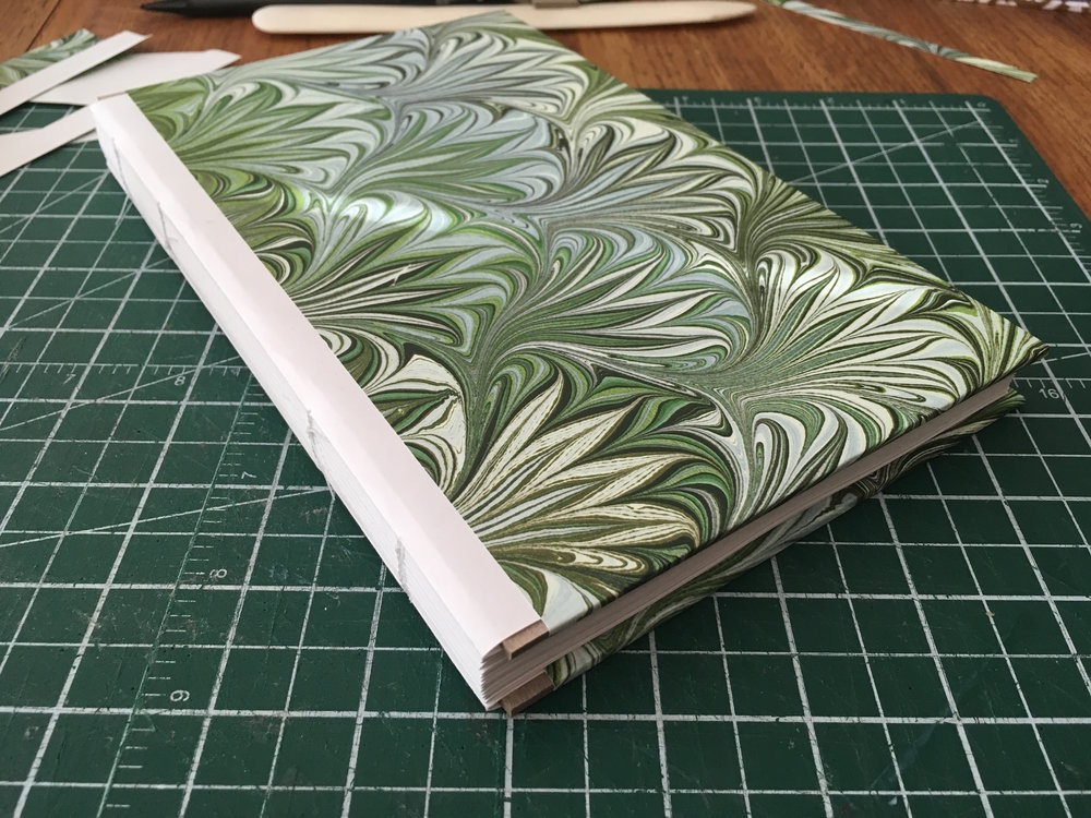 Step 6: - Now I'm ready to work on the spine. I can't use glue on the text block directly, remember - any moisture might warp the paper - so the spine is only going to be attached to the cover.