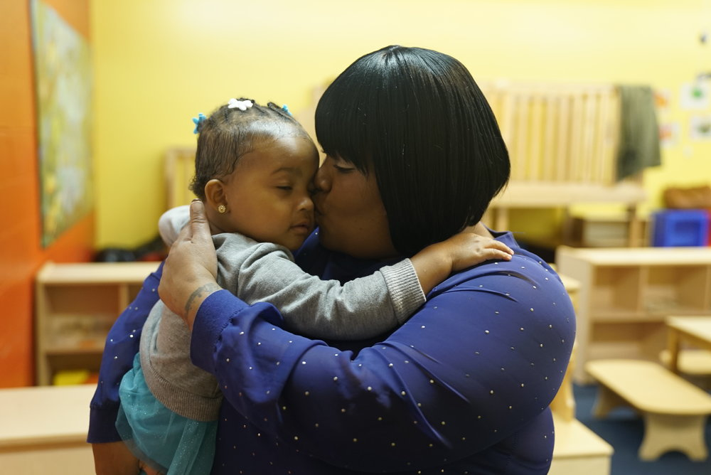 """After Ya-Ya was separated from me, Mother's Day in prison was the hardest time of my life. Ya-ya had a birthday was on Saturday and Mother's Day was on Sunday. The women around me were there to support me. Women build each other up in prison because our love is all you have."" – Delaisia   Timeline    2013  Delaisia, who was working as a nurse, is incarcerated while pregnant.  2014  Delaisia gives birth to Ya-Ya in prison. She sends Ya-ya to her family to take care of her.  2015  Delaisia is released from prison and interns as a receptionist at Hour children. There she receives her GED and is now enrolled in school to become a registered nurse   Biography   Delaisia is the mother of Ya-Ya and is in training to become a registered nurse.  Delaisia was working towards being a certified nurse assistant and was one month pregnant when she was arrested for selling drugs and collecting unemployment while working. Today Delaisia is taking classes in the field of medicine and is interning as a receptionist. She is teaching her two-year-old daughter Ya-ya to read, cook, and attend church together. Her experiences have taught her that kindness is invaluable toward survival. She strongly believes that small crimes are not equivalent to the trauma faced while incarcerated and forced to be separated from her family. She attributes her resilience and love to her loving family of nurses and strong women.  ""My daughter is teaching me how to love again. That in order to love her, I need to love myself."""