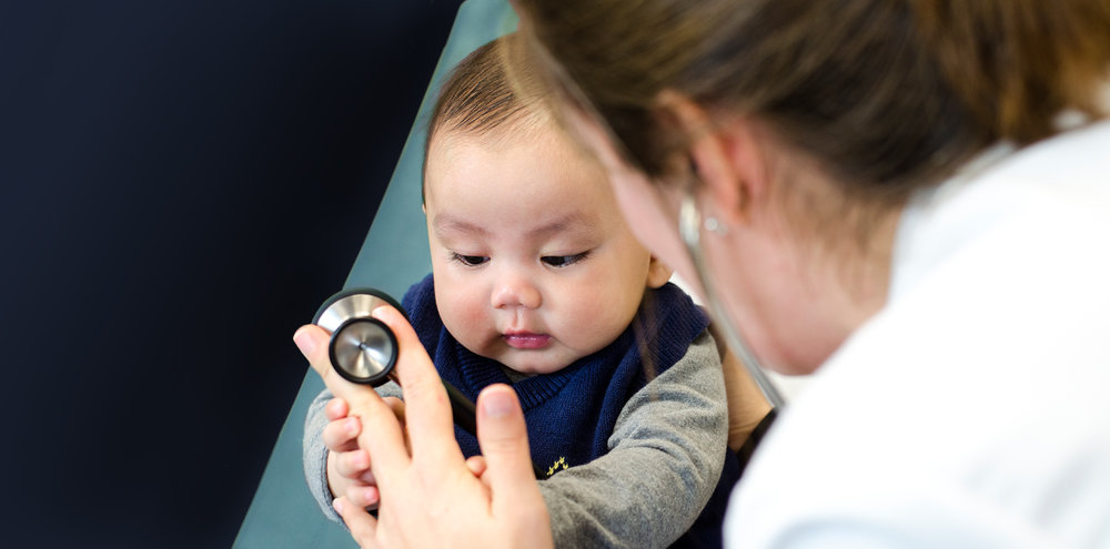 Baby holding stethoscope with doctor