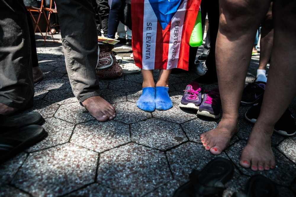 Protestors symbolically participate by removing their shoes in solidarity with the #4645Boricuas who are now estimated to have lost their lives after Hurricane Maria wreaked havoc in Puerto Rico.  Learn more about our direct action at the United Nations:  No Refuge from the Storm on Saturday, June 2 in this article in the New York Times:  Protestors Demand Audit of Hurricane Maria Death Toll in Puerto Rico .  Photo credit: Jeenah Moore for the New York Times