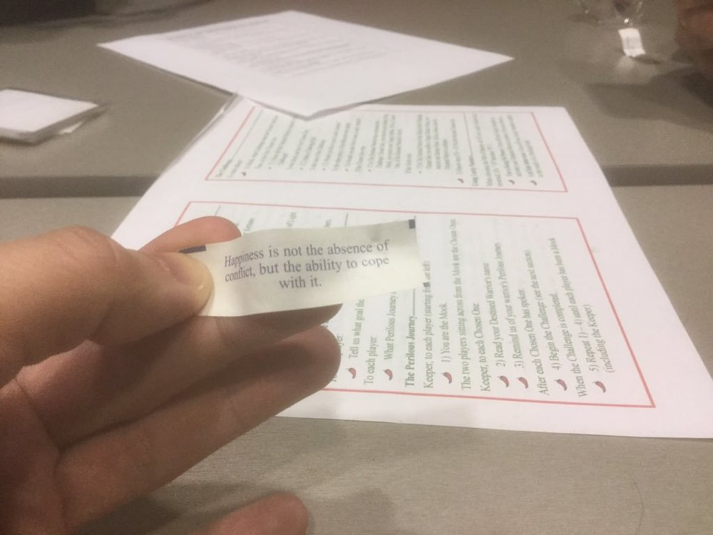 """Mendez's hand with a fortune that reads, """"Happiness is not the absence of conflict, but the ability to cope with it."""" Behind him on the table are some game materials, one of which is a rules cheat with green text and red borders like a Chinese menu. And chili pepper bullet points."""