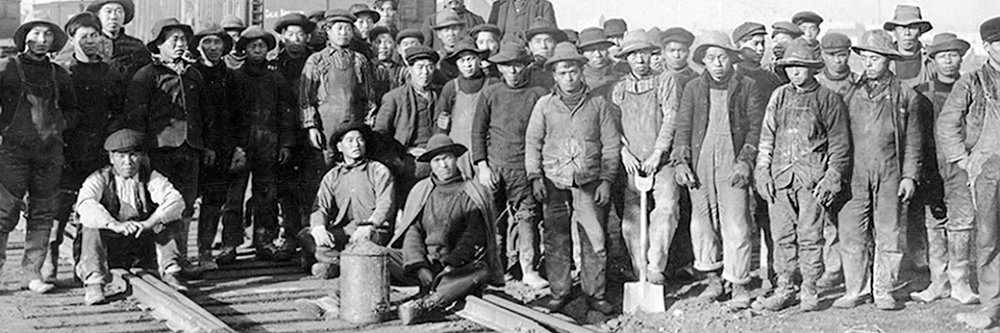 A black-and-white photo of many Chinese railworkers posing on a rail line. From the Chinese Railroad Workers' Memorial Project.