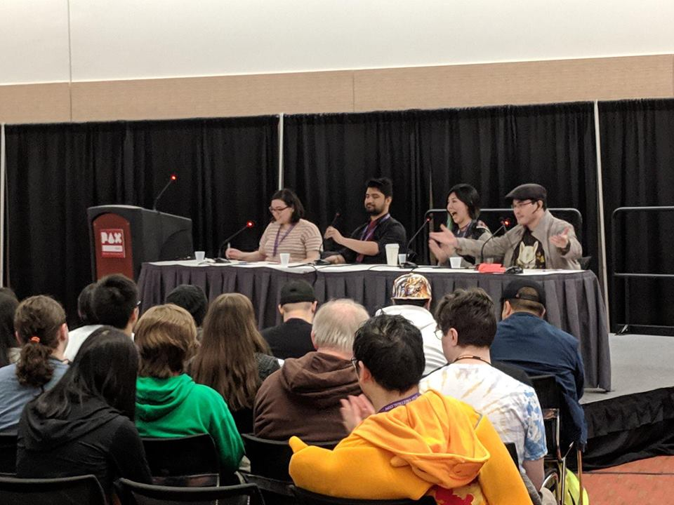 Viewed from the audience, panelists Clio, Sharang, Banana, and Mendez speak to an audience at the PAX East convention on Saturday 2019-03-30 in Boston, Massachusetts.