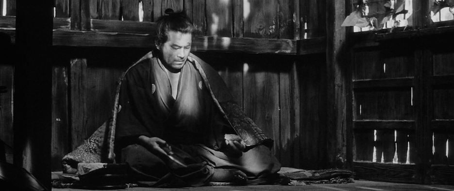 Mifune Toshirō, the only Asian man it is truly safe to be, as Tsubaki Sanjūrō in  Yōjinbō.  He's sitting in a shack practicing his knife-throwing.