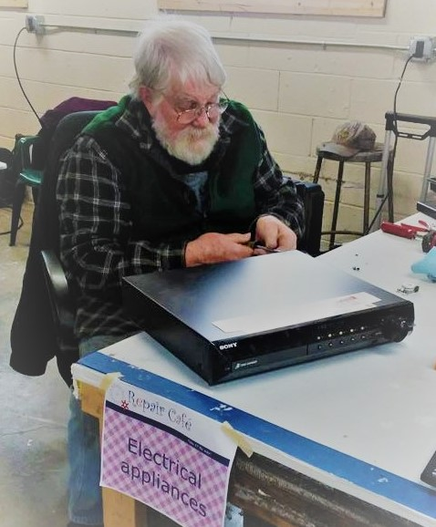An experienced volunteer at my local Repair Cafe is helping this DIY repair newbie to fix my DVD player.    Photo by: MaryEllen Etienne