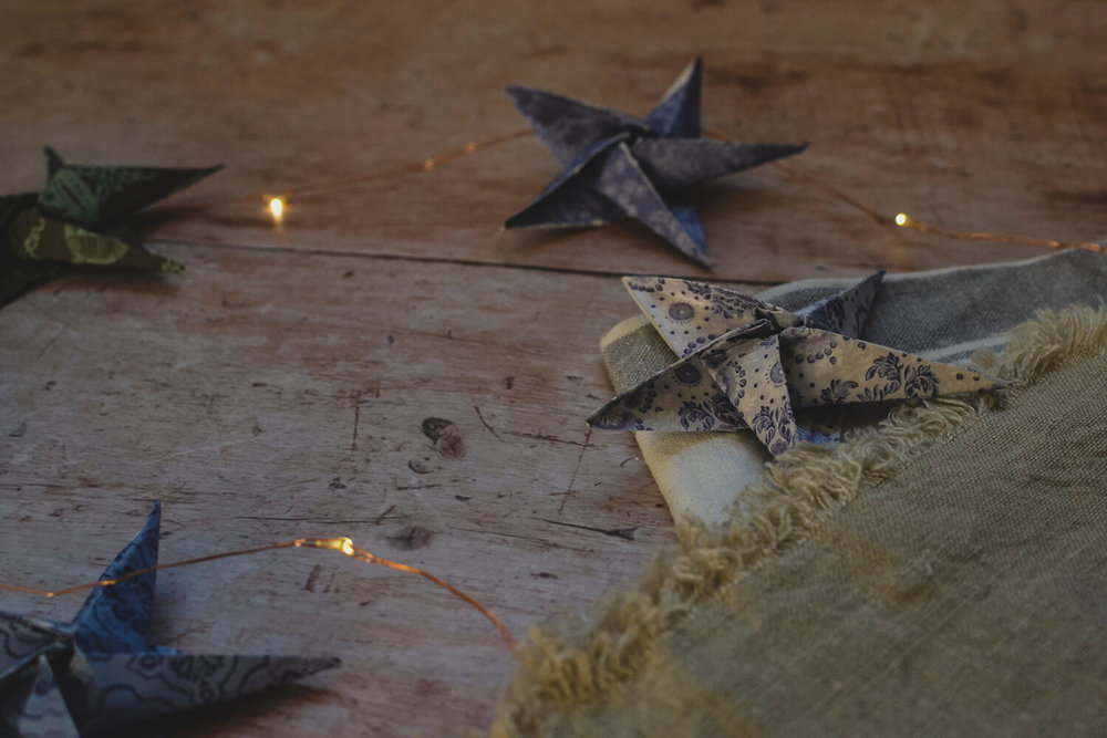 Origami stars on a rustic table with fairy lights