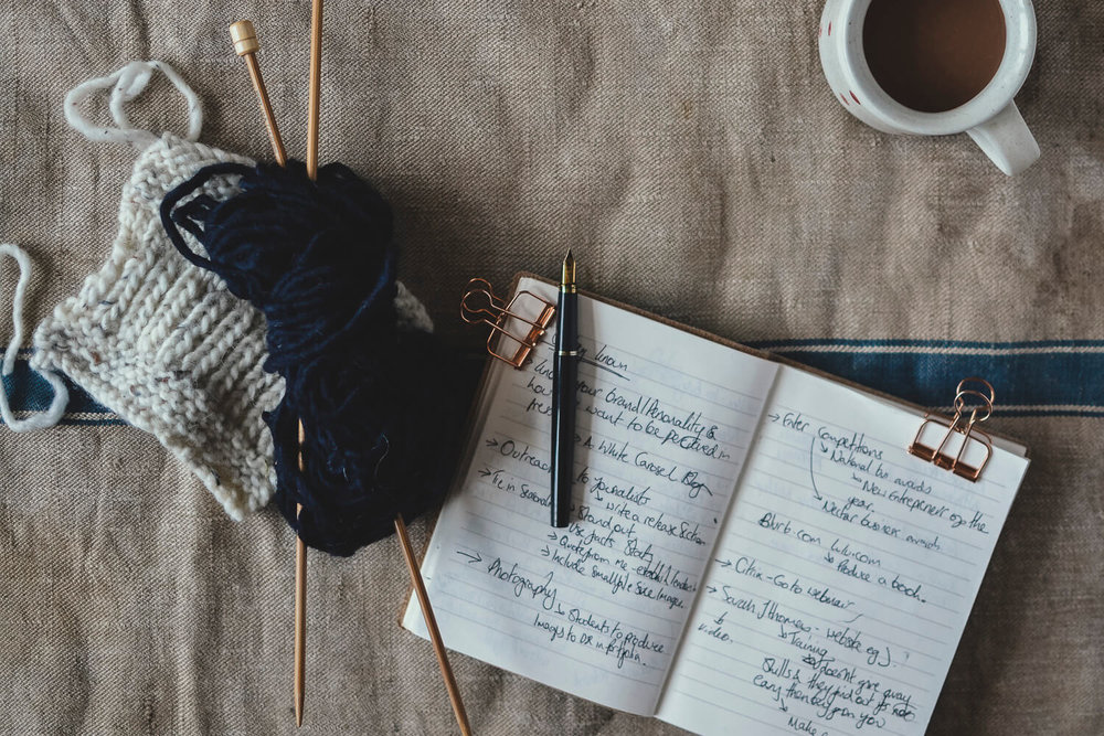 Open notebook with a ball of wool and cup of tea - creative business plan