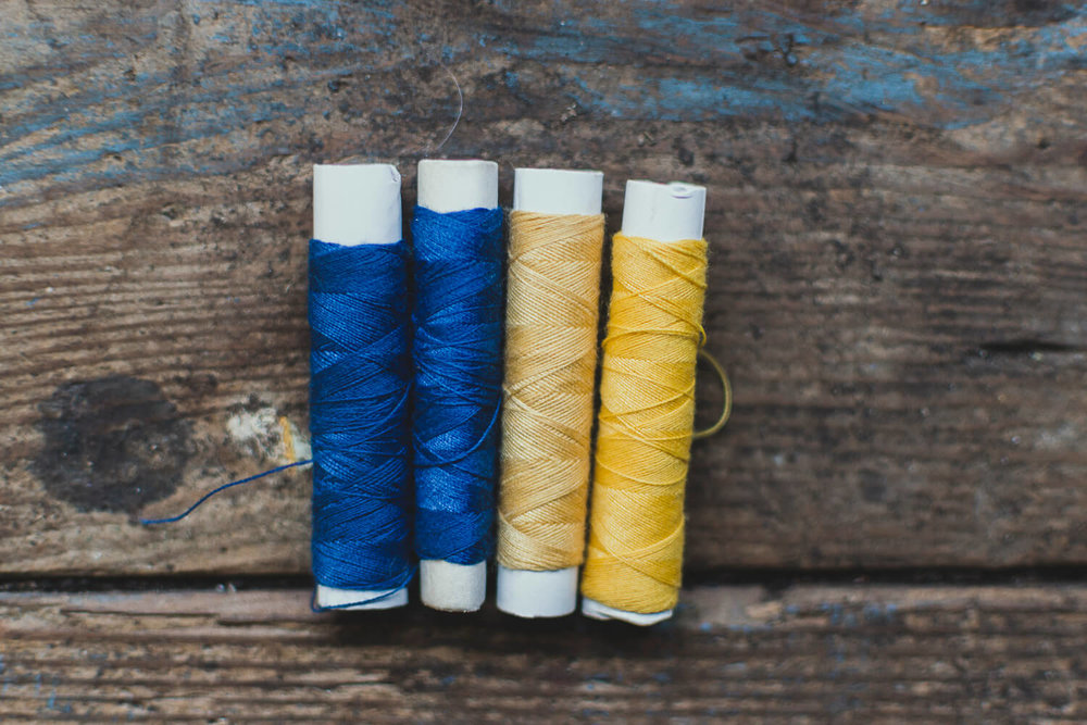 Blue and Yellow sewing threads in a rustic wooden table - creative business planning