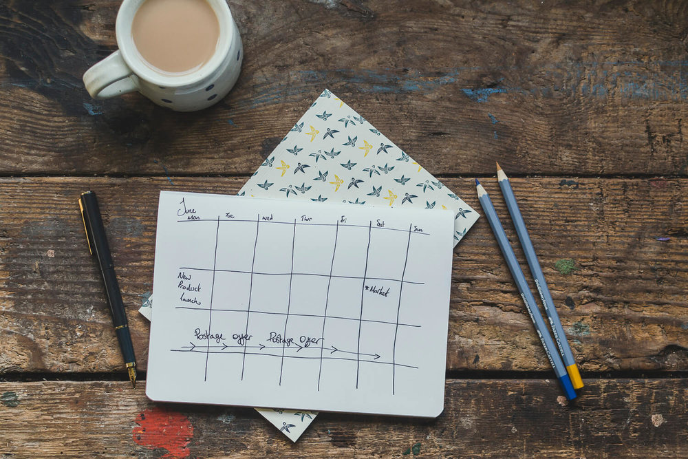 Pens and notebooks on a rustic table with a cup of tea - making a plan - Creative business planning - where to start