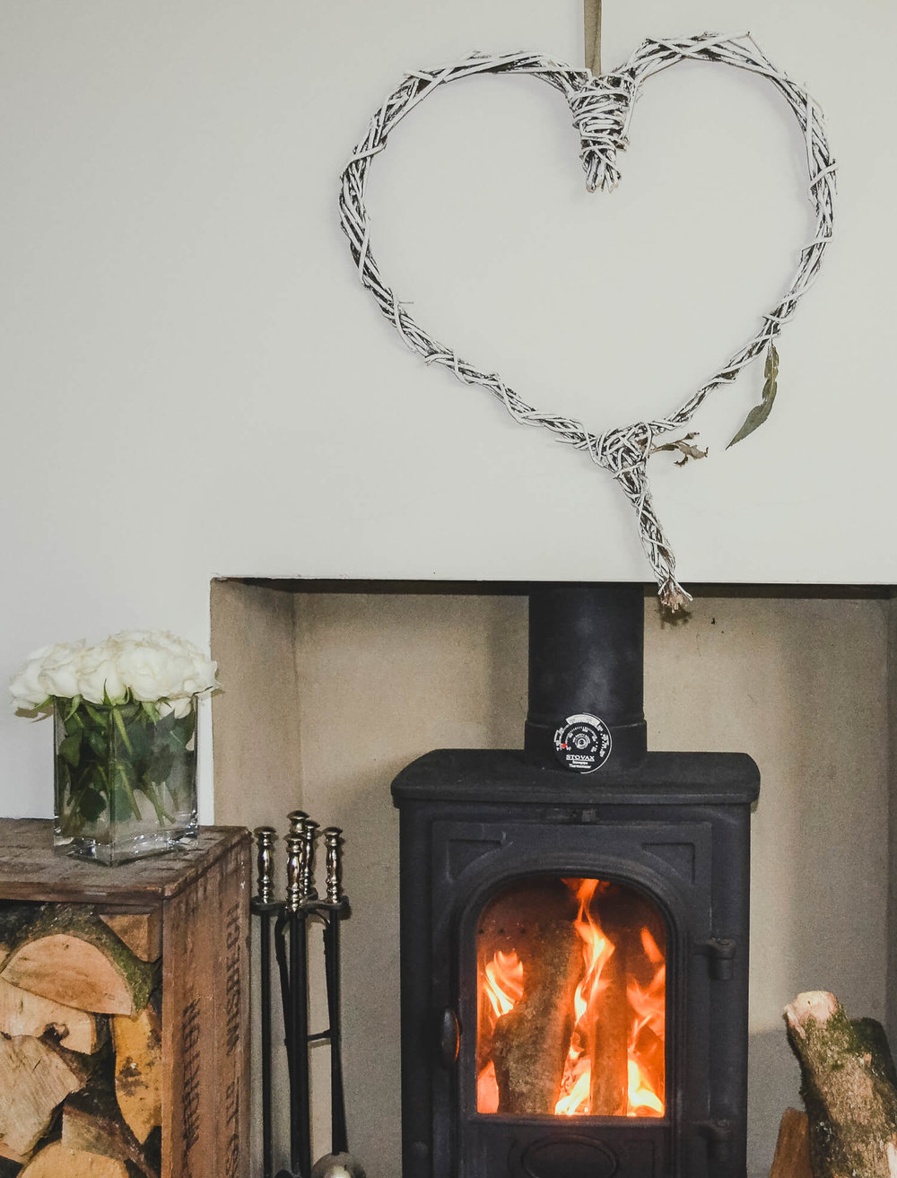 Willow heart decoration hung above a roaring fire with piles of logs