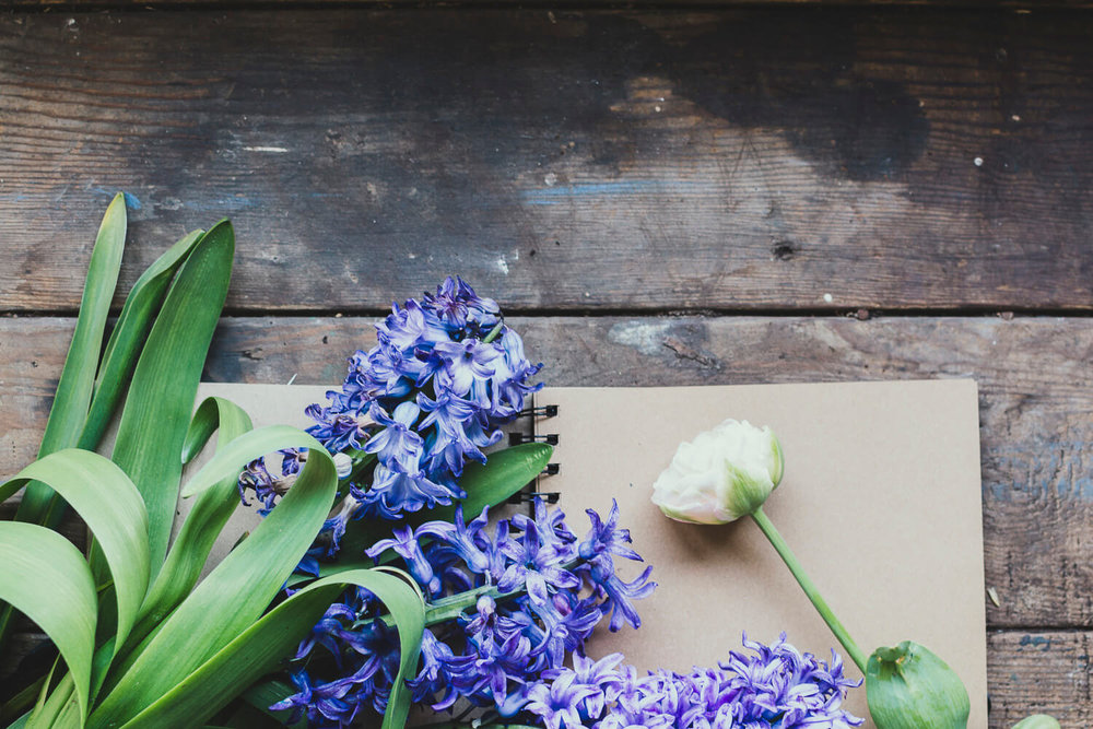 Blue hyacinths and tulips on a rustic wooden table - managing your time when you have a business and a job