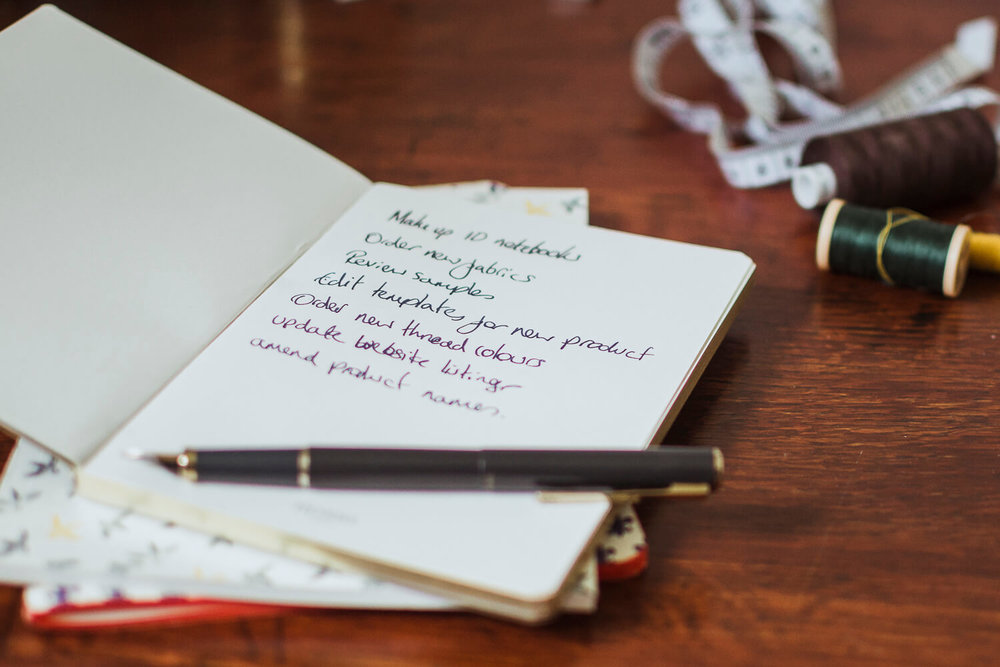 Notebook and pen on a dark, wooden desk - How to manage overwhelm in a creative business