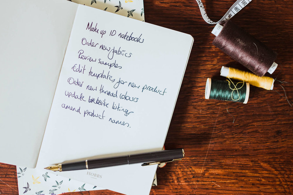 Notebooks, writing lists on a desk with measuring tape and threads - managing overwhelm