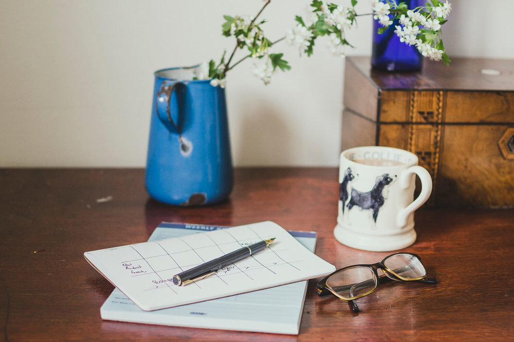 Notebooks, glasses and pen with a cup of tea on a wooden desk