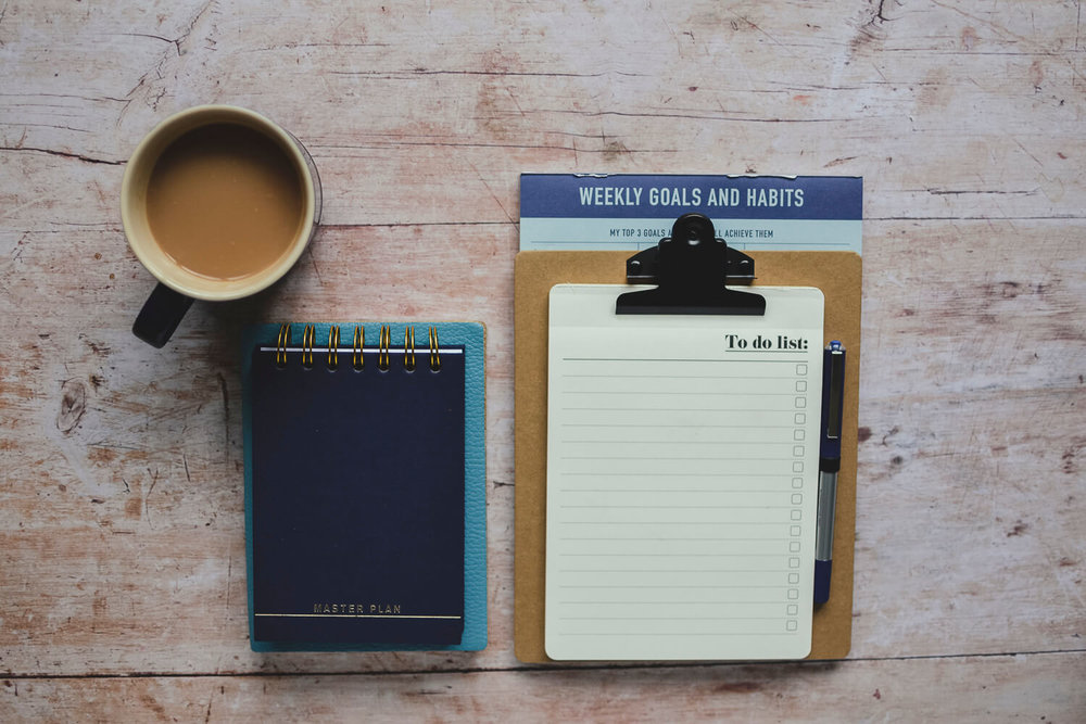 Notebooks and a to-do list on a rustic wooden table with a cup of tea - time management tips for creatives