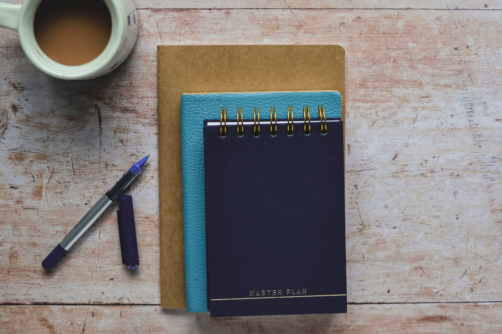Notebooks on a wooden table with a ribbon - managing your time for makers and designers