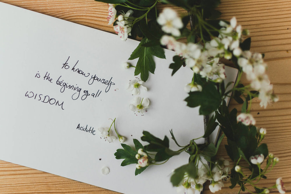 Quote handwritten in a notebook on a wooden table with spring blossom - To know one's self is the beginning of all wisdom - Aristotle