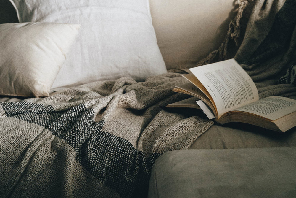 Open book on a sofa covered in blankets and cushions