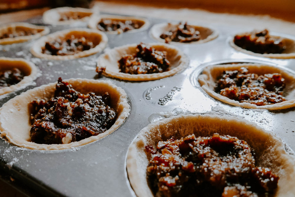 Homemade mince pies being filled with mince meat ready to be cooked