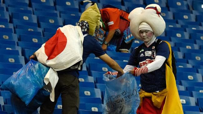 Fans of Japan clean up the stadium after watching their team (Courtesy of  Agence France-Presse)