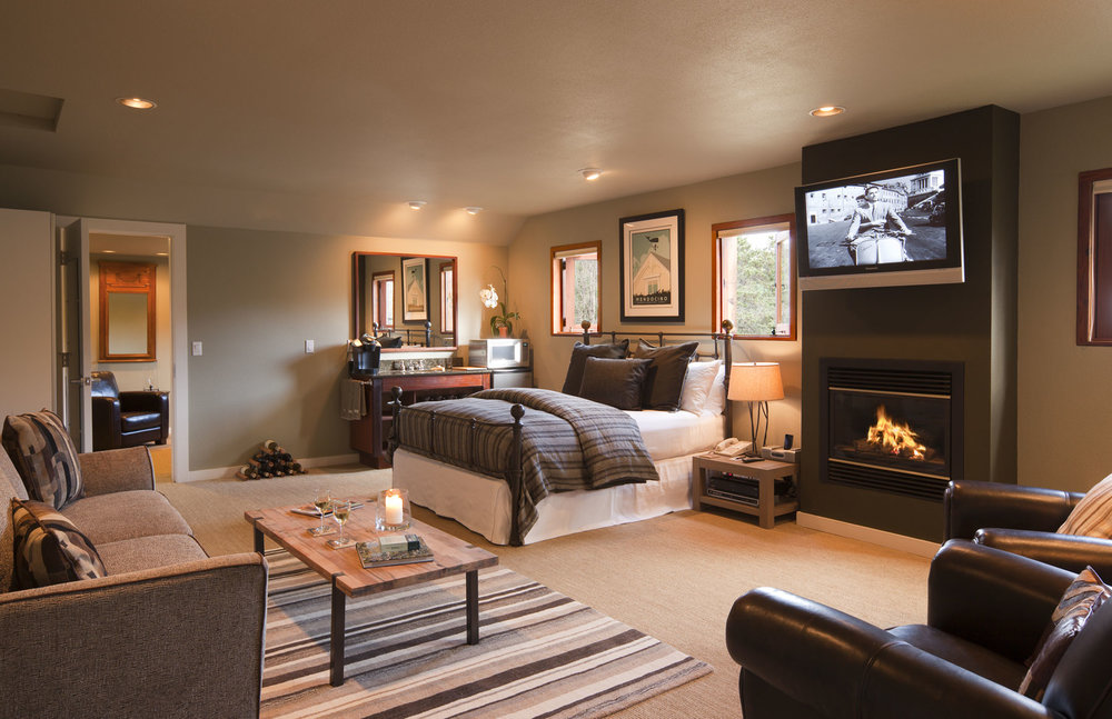 Meadowview Second Floor suite with two rooms, King bed, sofa, flat screen TV, and fire in fireplace.