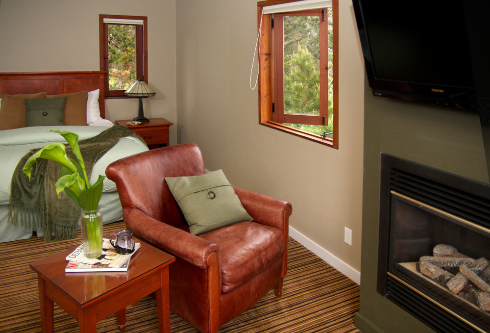A comfortable leather chair in front of the fireplace in the Osprey room